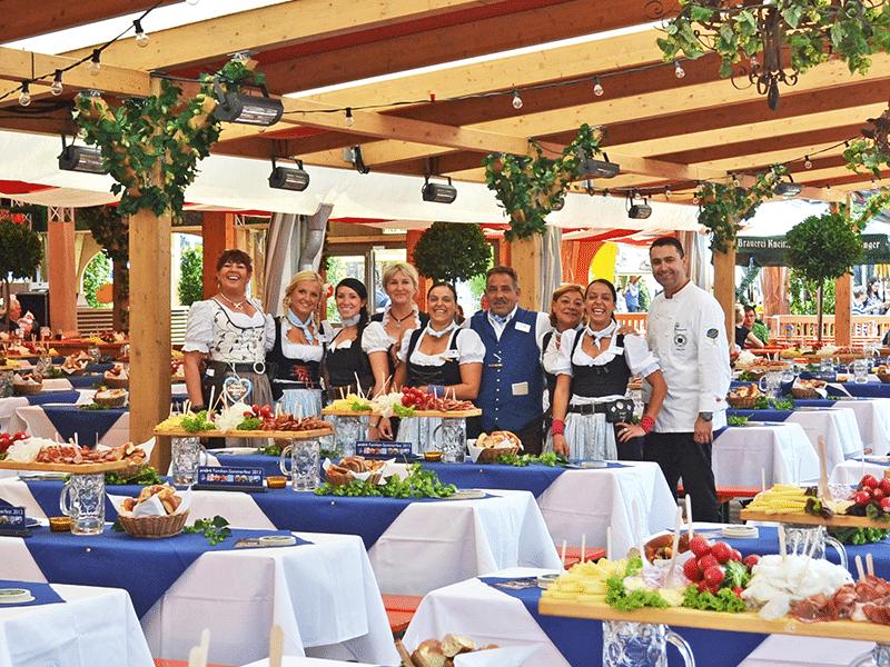 Kellnerinnen und Kellner im Hahn Zelt vor gedeckten Tischen im Volksfestzelt